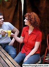 Redhead MILF and her young lover fucking each other outside on the garden's bench